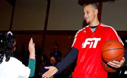 Photo of Stephen Curry high-fiving a young girl