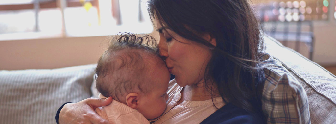 Photo of a woman kissing a baby